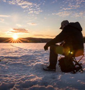 man ice fishing on a lake