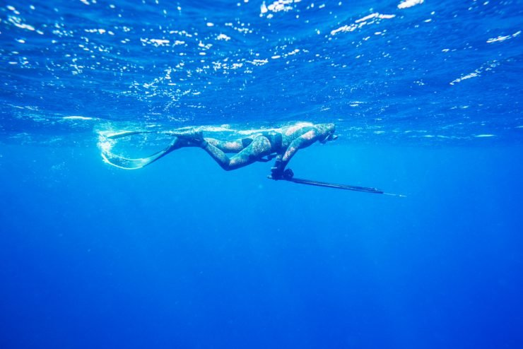 a man spearfishing a reef