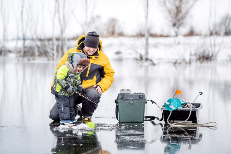family ice fishing on a lake