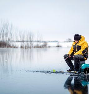 guy ice fishing on lake