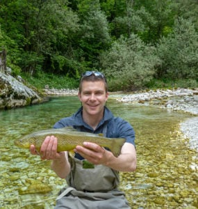 a fisherman holding a rare marble trout
