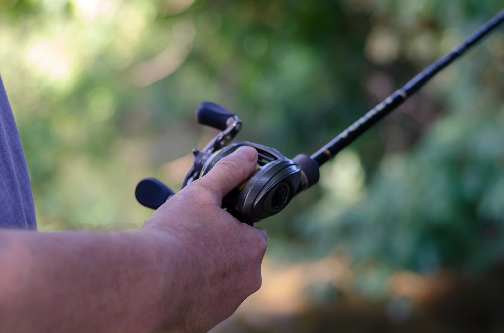 The male hand holds the baitcasting reel
