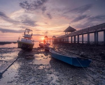 Early morning scenery of stranded boats by beach during low tide at fishermen`s jetty