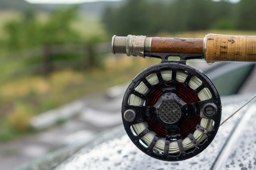 Fly fishing rod and reel close up covered in water