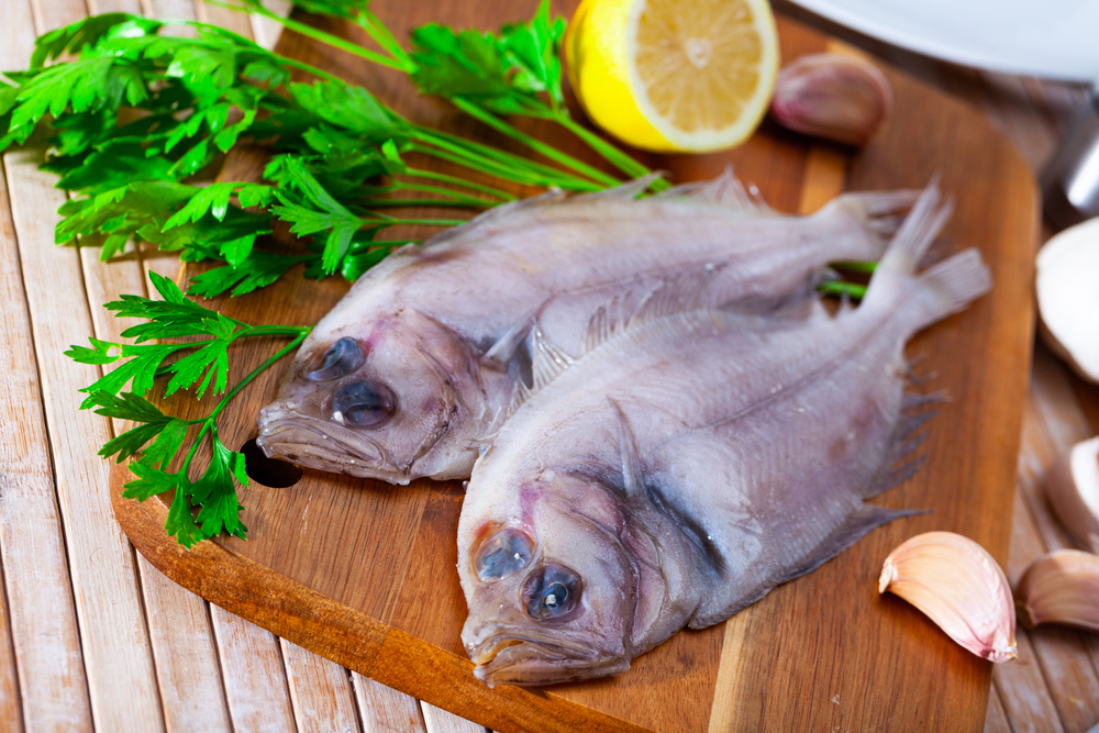 Megrim Flatfish on a chopping board with parsely with lemon