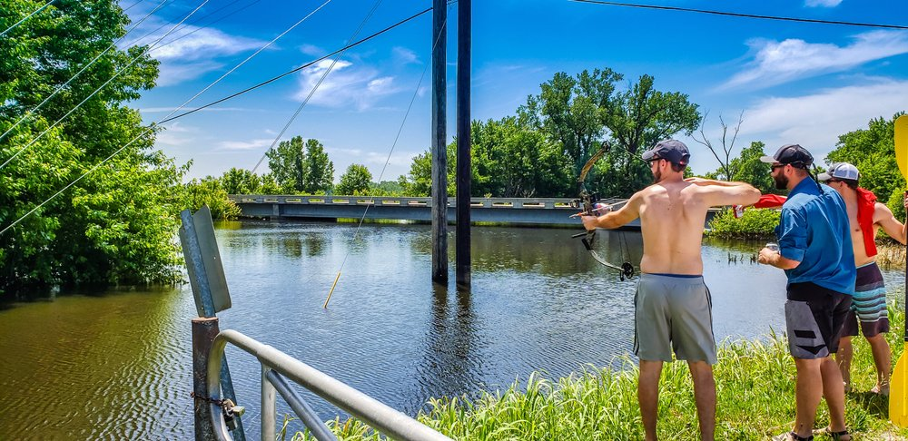 Three men fishing with bow and arrow in Missouri